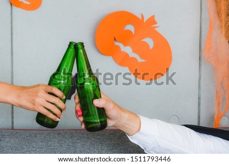 Halloween party, People in spooky costume clink bottles and cheer from celebrating holiday event