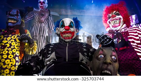 Halloween party scary clowns. Horror clown leader sitting in the electric chair surrounded by terrifying clowns.