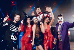 Halloween party. Six friends in costume cine villains posing at a party for Halloween. Around them flies confetti. They are having fun and laughing