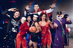 Halloween party. Six friends in costume cine villains posing with skull and pumpkin-lamp at a party. Around them flies confetti. They are having fun and laughing