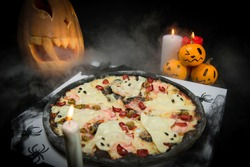 Halloween party table decoration. Ghost pizza near spider web, pumpkin jack o lantern And black bats. Candle lights on foggy background. Fast food with cheesy silhouettes served on takeaway pizza box.