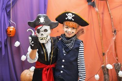 Halloween party. Two little boys in different pirate costumes with faceart are having fun at the Halloween party. Face painting kids.