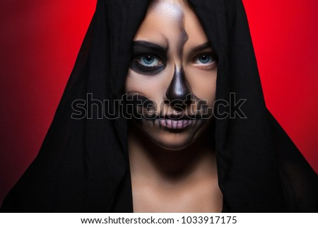 Stock Photo Halloween. Portrait of a young beautiful girl with skeleton makeup on her face. Girl in black hood on a bright red background