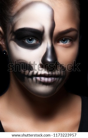 Stock Photo Halloween portrait of young beautiful girl in a black hood. skeleton makeup half face