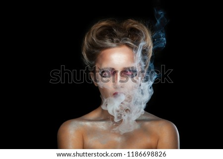 Stock Photo Halloween. Portrait of young beautiful girl with make-up. E-cigarette smoke, Viper. Isolated on black background.