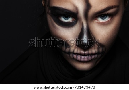 Stock Photo Halloween. Portrait of young beautiful girl with make-up skeleton on her face