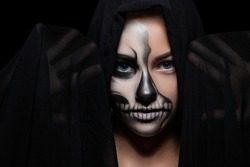 Halloween. Portrait of young beautiful girl with make-up skeleton on her face. Black background