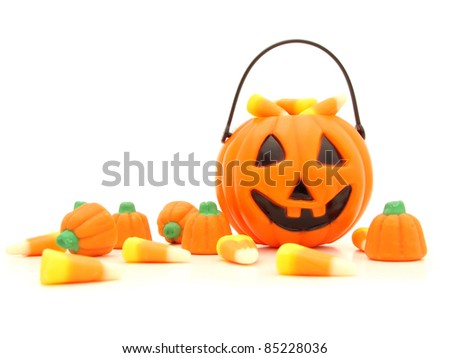 Halloween pumpkin and a pile of scattered assorted candies against a white background