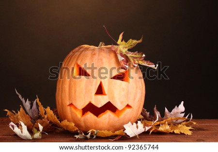 Halloween Pumpkin and autumn leaves on wooden table on brown background