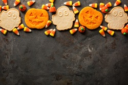 Halloween pumpkin and ghosts cookies and candy overhead shot with copy space