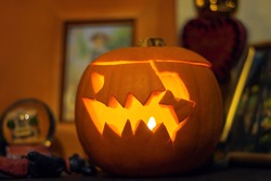 Halloween pumpkin carved lantern. Scary pumpkin face with a burning candle inside