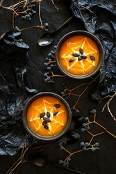 Halloween pumpkin cream soup with creamy spider web sprinkled with pumpkin seeds in black bowls on a dark background top view