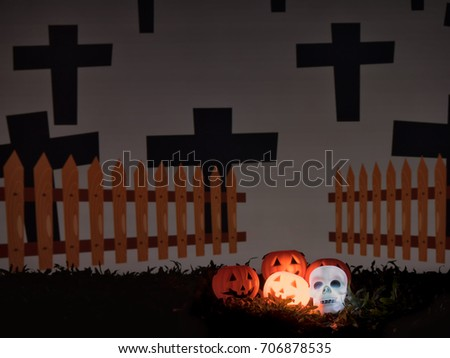 Halloween pumpkin face and skull glows glowing behind the cemetery and the cross in the dark night. #706878535