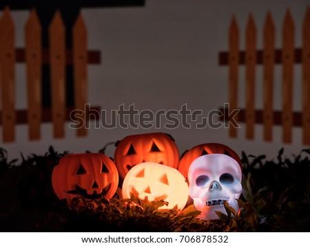 Halloween pumpkin face and skull glows glowing  in the dark night. #706878532