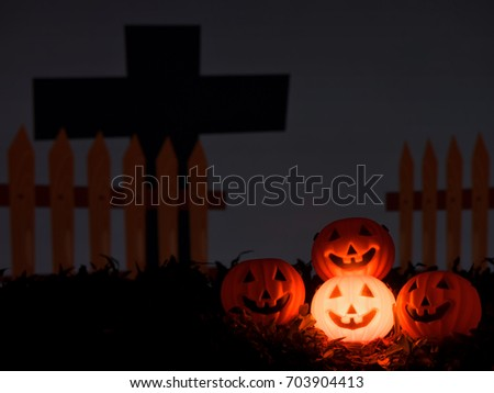 Halloween pumpkin face glows glowing behind the cemetery and the cross in the dark night. #703904413