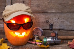 halloween pumpkin head in hat with fishing tackles on wooden boards background