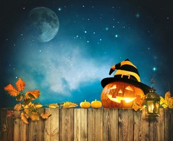 Halloween pumpkin head jack lantern on wooden fence