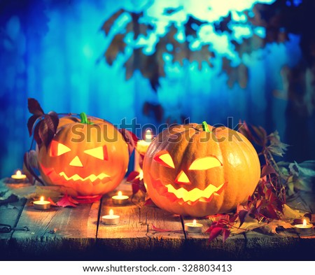 Halloween pumpkin head jack lantern with burning candles. Halloween holidays art design, celebration. Carved Halloween Pumpkins with burning candles in scary deep night forest #328803413