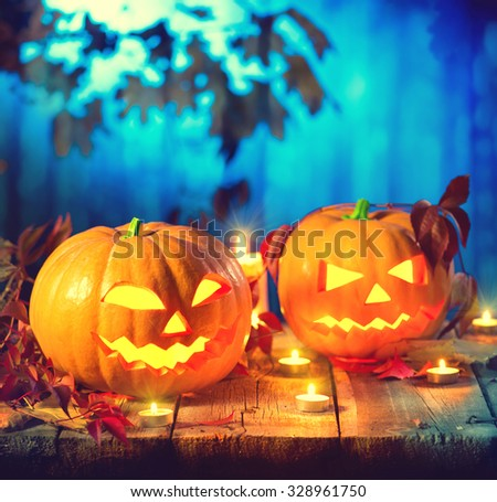 Halloween pumpkin head jack lantern with burning candles. Halloween holidays art design, celebration. Carved Halloween Pumpkins with burning candles in scary deep night forest #328961750