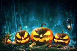 Halloween pumpkin head jack lantern with burning candles in scary deep night forest