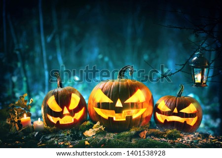 Halloween pumpkin head jack lantern with burning candles in scary deep night forest #1401538928