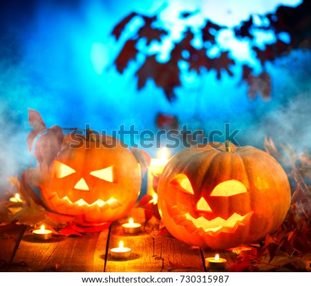 Halloween pumpkin head jack lantern with burning candles over wooden background. Halloween holidays art design, celebration. Carved Halloween Pumpkins with burning candles #730315987