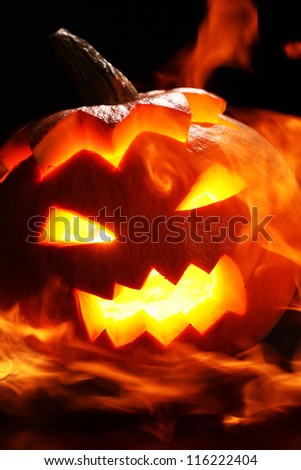 Halloween pumpkin in fire over a black background