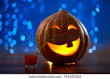 Halloween pumpkin jack face lantern with a candle burning placed on the table with a cocktail copyspace party festive celebrating mood fun autumn concept. #742420582