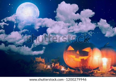Halloween pumpkin Jack-o'-lantern on wooden table with candles in a spooky night over moon and clouds. #1200279946