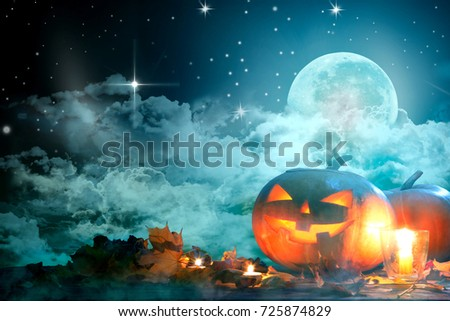 Halloween pumpkin Jack-o'-lantern on wooden table with candles in a spooky night over moon and clouds. #725874829