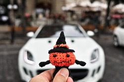 Halloween pumpkin man on the background of a sports car on the street