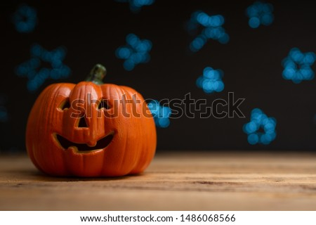 Halloween pumpkin on a background of blue blurry stars, lights. With space for design, festive mood