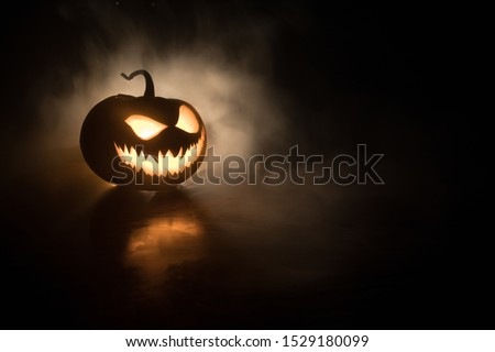 Photo of  Halloween pumpkin smile and scary eyes for party night. Close up view of scary Halloween pumpkin with eyes glowing inside at black background. Selective focus
