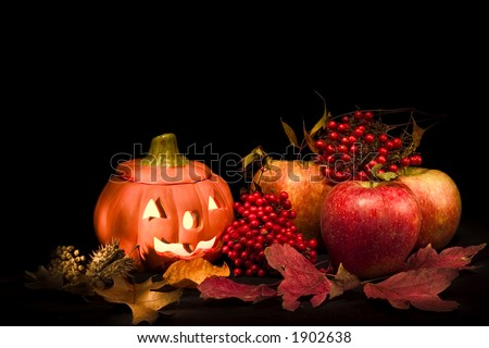 halloween pumpkin with apples and autumn leaves over black