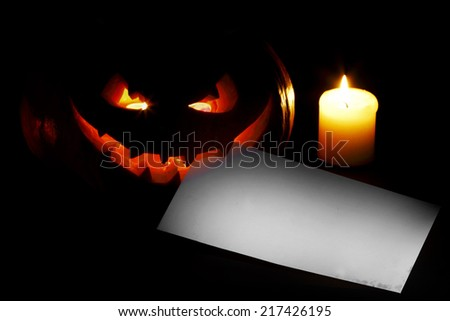 Halloween pumpkin with blank post card and candle on black background