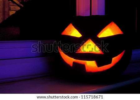 Halloween pumpkin with scary face on the window at night