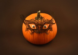 Halloween pumpkin with sexy lace mask stock images. Seductive halloween pumpkin on a dark background. Black lace mask on pumpkin. Halloween pumpkin with eyes stock images