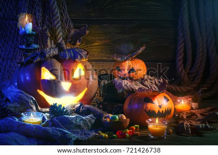 Halloween pumpkins and candy on wooden table at night. #721426738