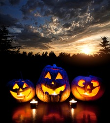 Halloween pumpkins glowing inside at forest and sunset evening sky background