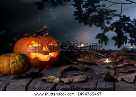 Halloween pumpkins head jack o lantern and candles on wooden table background in a mystic  forest at night. Halloween design with copyspace.