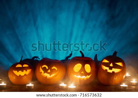 Halloween pumpkins in a row with candles over blue light rays and smoke at background with copy space for text above, front view #716573632