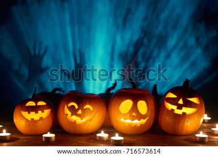 Halloween pumpkins in a row with candles over blue light rays and smoke with human hands silhouette at background, front view #716573614