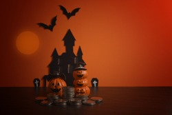 Halloween pumpkins jack-o-lantern with money coin stack growing business on orange background. Happy Halloween.