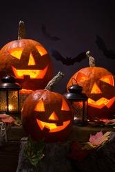 halloween pumpkins, near lanterns and  bats on dark background