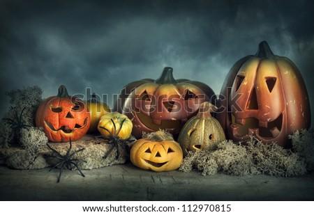 Halloween pumpkins on a wooden desk at night