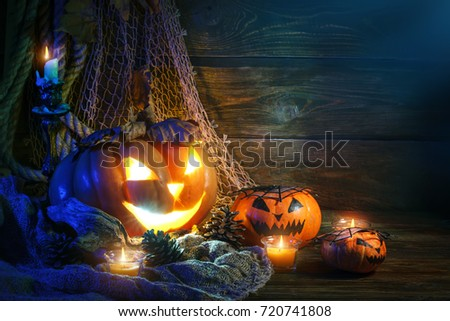 Halloween pumpkins on a wooden table at night.