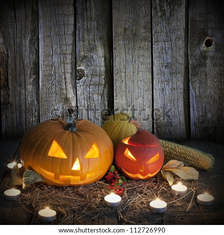 Halloween pumpkins on old grunge boards and candles background