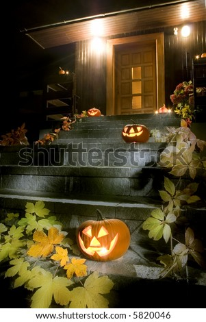 halloween pumpkins on stairs in front of the house at night