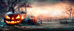 Halloween Pumpkins On Table With Spiderweb In Gloomy Landscape