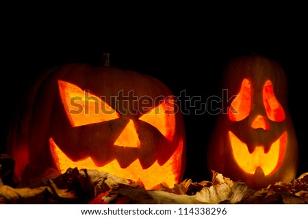 Halloween pumpkins over dried leaves - stock photo